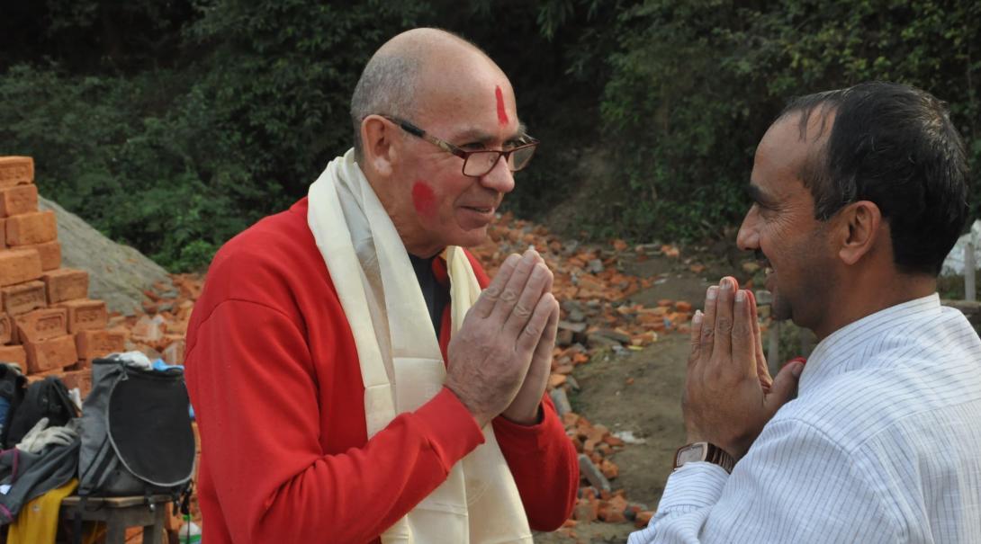 En äldre volontär blir varmt välkomnad till Nepal av sin värdfamilj.